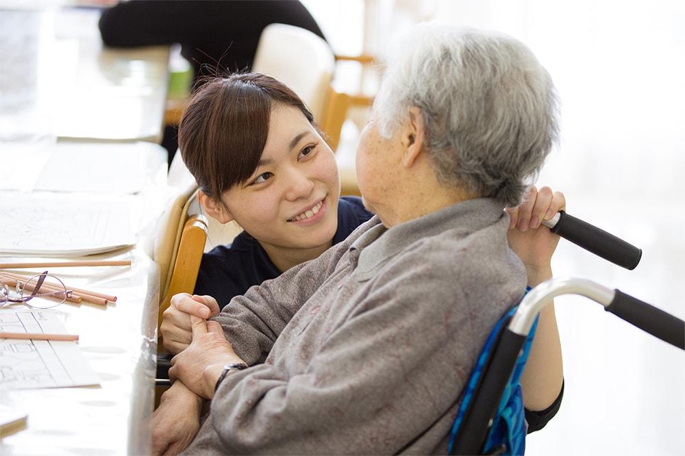笑顔でおばあさんに話しかけている介護士の写真