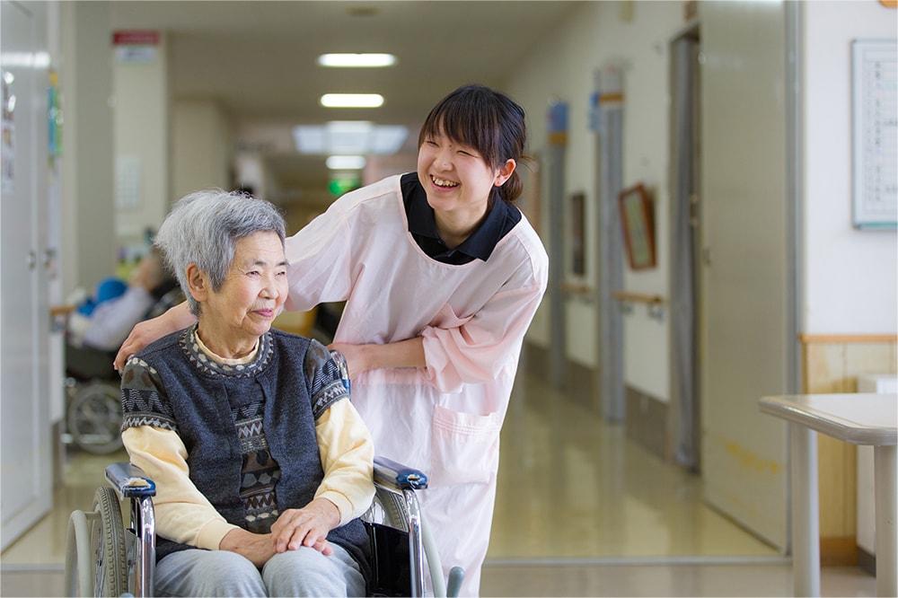 笑顔で車椅子を押す介護士の写真