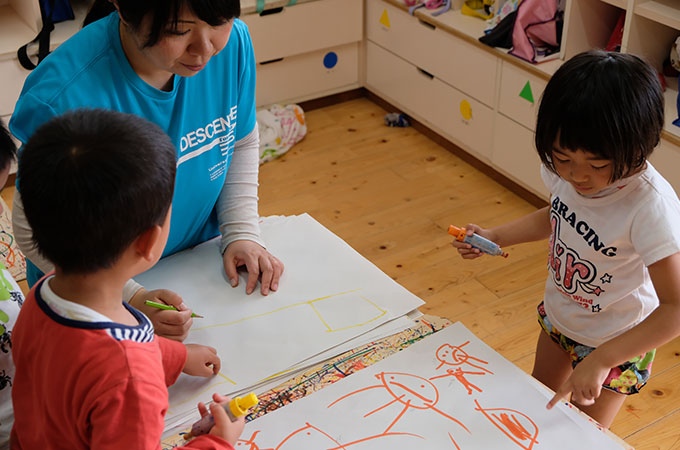 子どもに絵を書いてあげている先生の写真